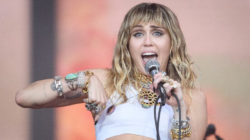 Miley Cyrus wears a white crop top and sings onstage during an outdoor performance