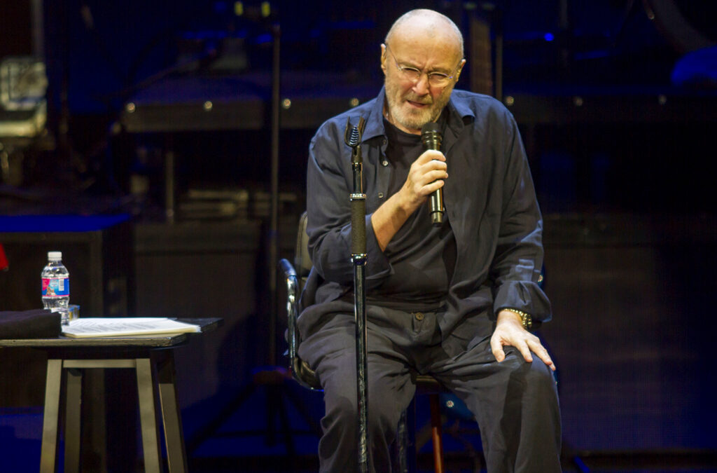 Phil Collins performing, seated, on stage.