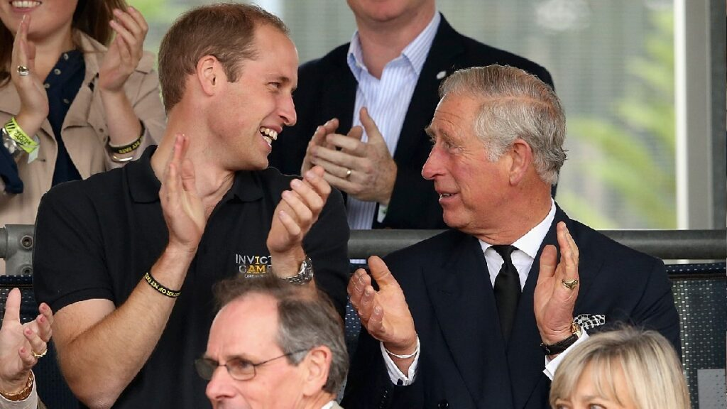 Prince William, in a black shirt, claps and smiles at Prince Charles, in a black suit, at the Invictus Games