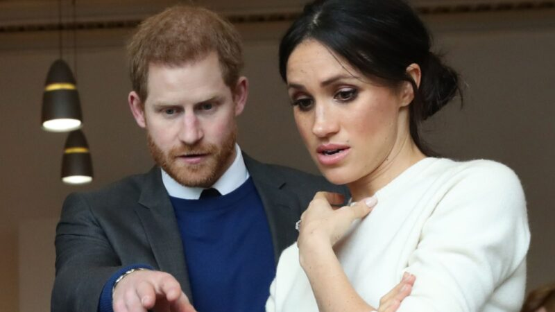 Prince Harry points at a prosthetic limb as Meghan Markle looks on