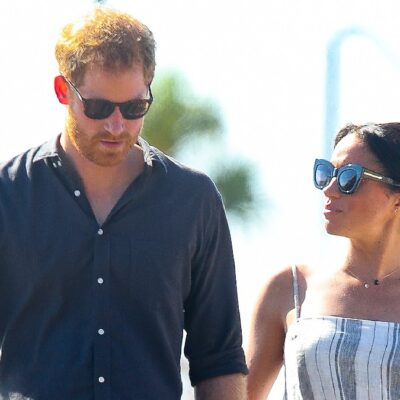 Prince Harry, in a dark shirt, walks outdoors with Meghan Markle, in a white dress