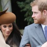 Meghan Markle wears a tan coat and walks with Prince Harry, in a gray coat