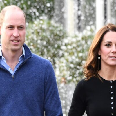 Prince William, in a blue sweater, walks with Kate Middleton, in a black top, outdoors