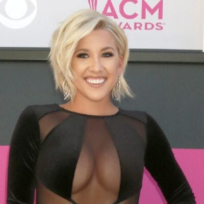 Savannah Chrisley wears a black dress against a pink and black background