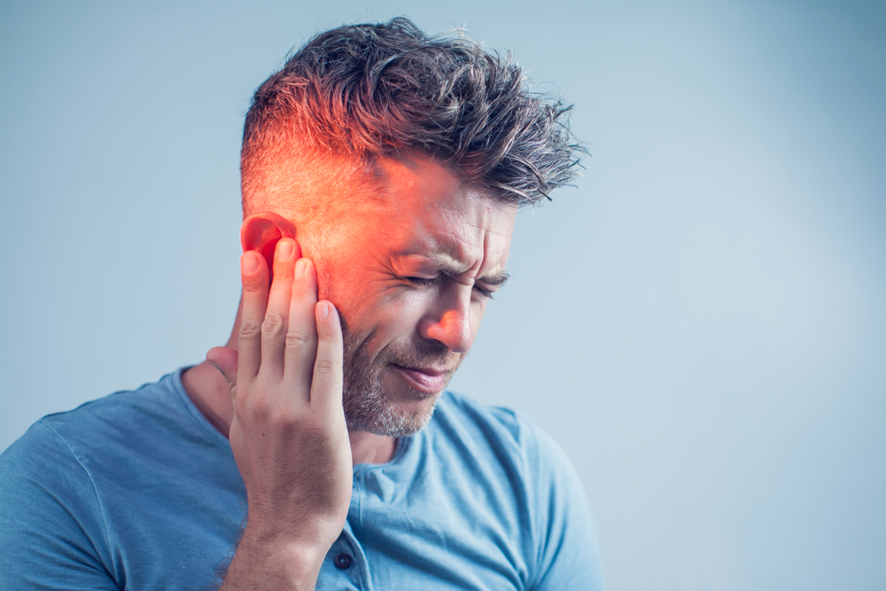 Man scrunching face with his hand to his ear, his ear and side of face red to indicate pain.