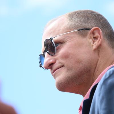 Woody Harrelson wearing sunglasses and blue jacket