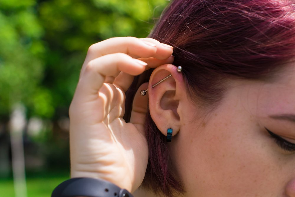 Woman tucking her hair behind her ear with an industrial piercing.