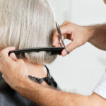 Closeup,Of,Male,Hairstylist,Measuring,Hair,Length,Before,Haircut,In