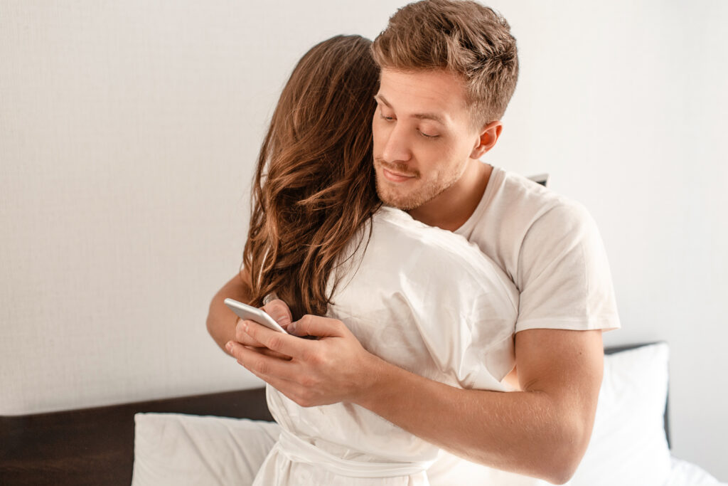 Boyfriend checking phone when hugging girlfriend
