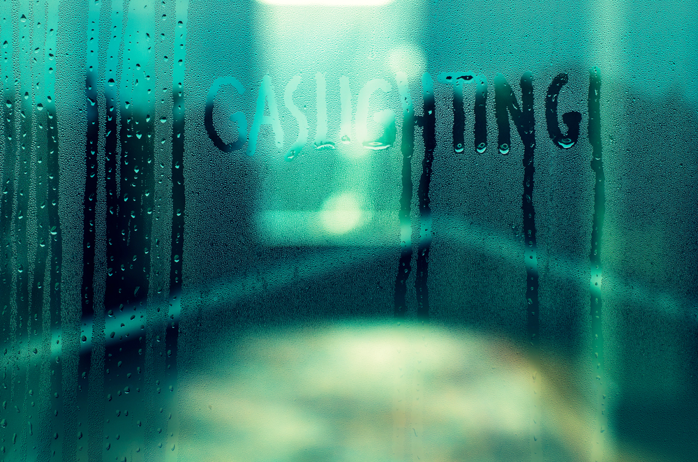 """""""Gaslighting"""" written in the condensation on glass with a green background."""