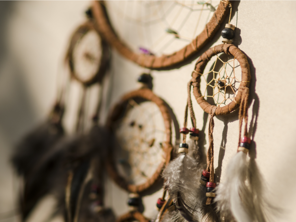 A brown dream catcher resting against a wall