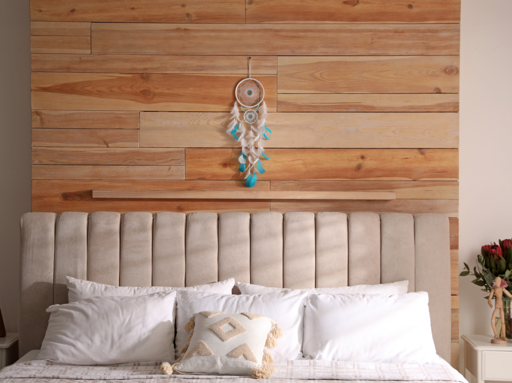 A white and teal dreamcatcher hangs above a bed