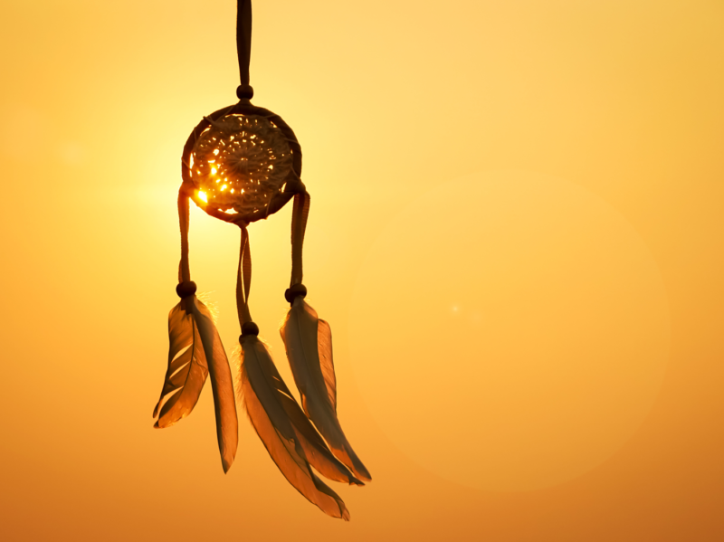 A dreamcatcher with large feathers hangs with a sunset in the background.