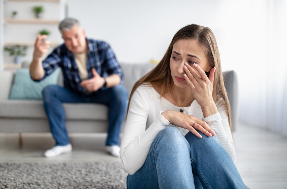 Stock photo of a woman crying in the foreground and a man yelling at her in the background.