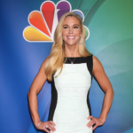 Kate Gosselin poses on an NBC red carpet in a white dress with black trim