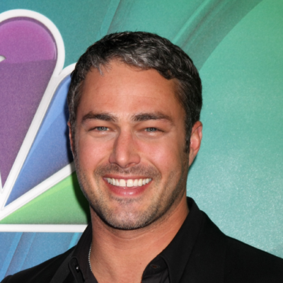 Taylor Kinney grins at the camera in a black button up shirt
