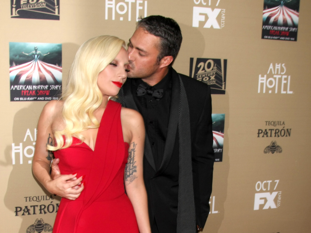 Lady Gaga, in a red dress, poses with Taylor Kinney