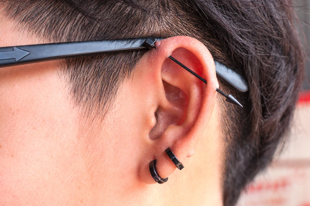 Closeup of an industrial piercing with an arrow barbell.