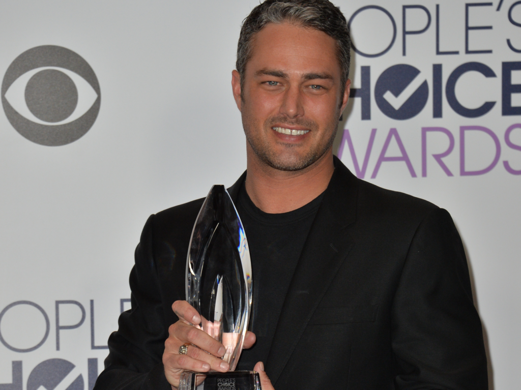 Taylor Kinney poses with an award in a black suit with black shirt