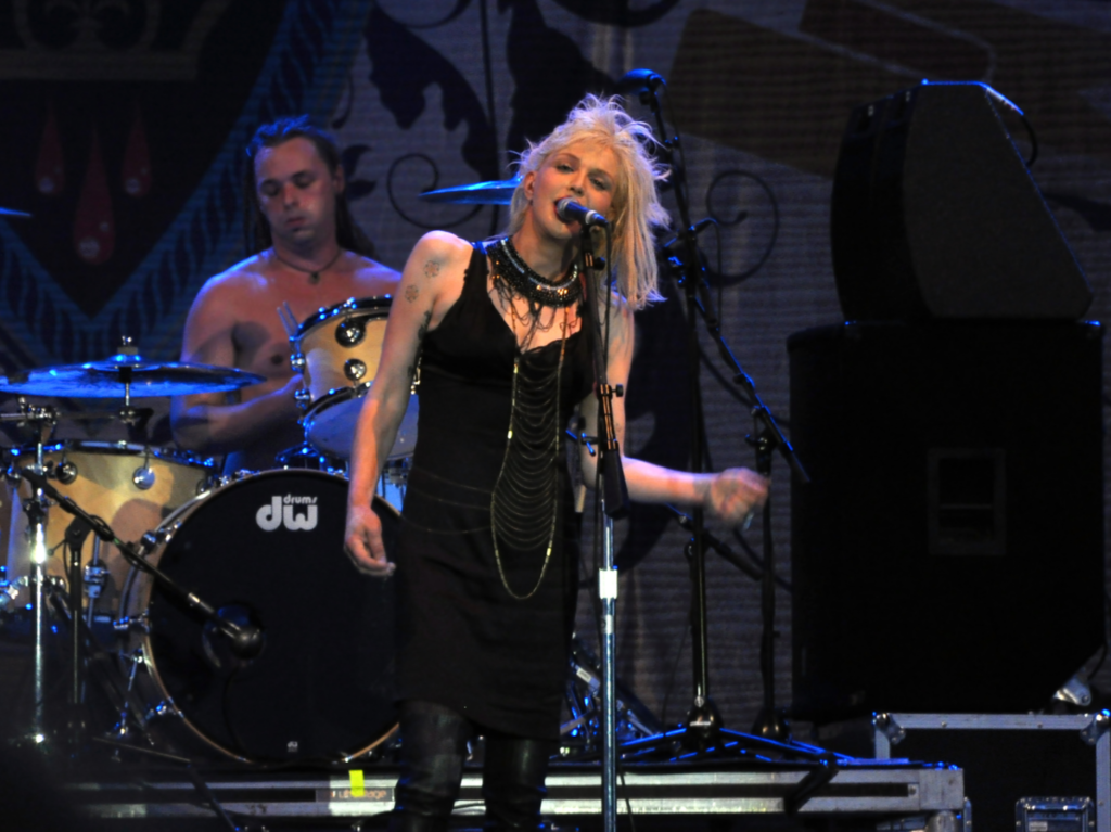 Courtney Love performs on stage in a grunge outfit