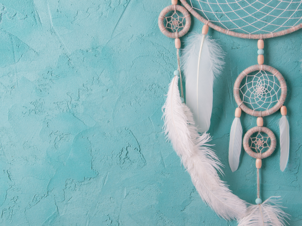 A white dreamcatcher rests against a blue background