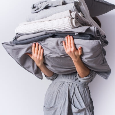 Image of woman holding piles of laundry.