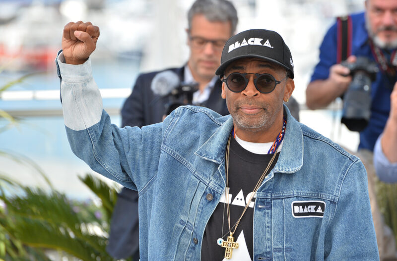 Spike Lee holding his right fist up in the air.