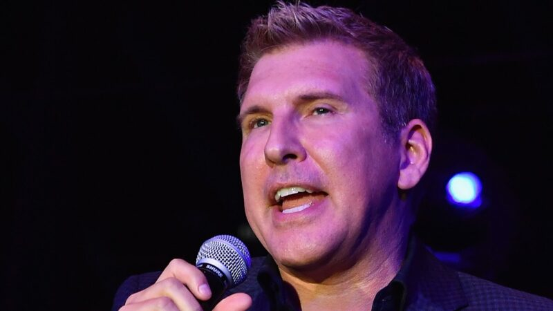 Todd Chrisley wears all black and addresses a crowd from the stage