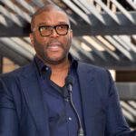 Tyler Perry in a suit, speaking into a microphone