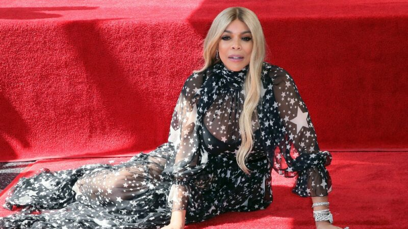 Wendy Williams wears a black dress and poses next to her Walk of Fame star