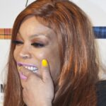 Wendy Williams uses a finger to scrub her teeth while wearing a black dress on the red carpet