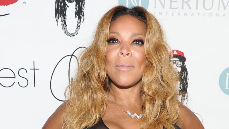 Wendy Williams poses in a black dress against a white background on the red carpet