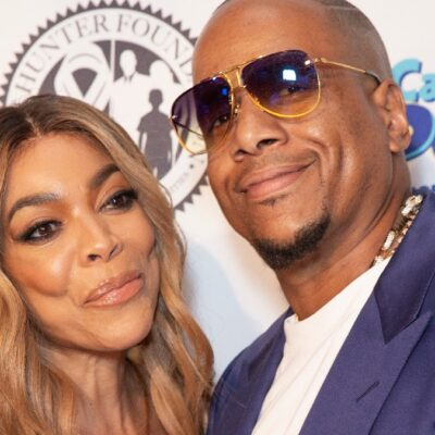 Wendy Williams wears a beige dress and poses with now ex husband Kevin Hunter, in a blue suit jacket