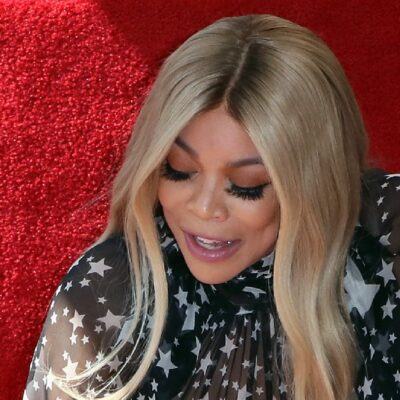 Wendy Williams wears a black dress against a red background and looks down