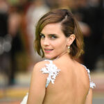 Emma Watson with her back to the camera, looking back over her left shoulder.