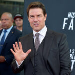 Tom Cruise waving in a grey suit