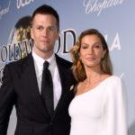 Tom Brady in a black suit with Gisele Bundchen in a white dress