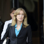 Felicity Huffman in a black coat and blue shirt