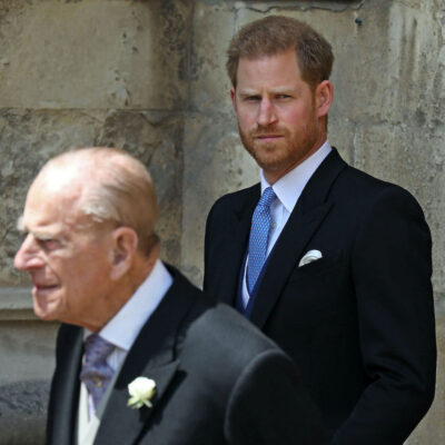 Prince Harry in a black suit looking at Prince Philip in a black suit