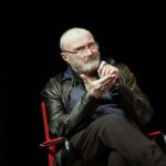 Phil Collins speaking on stage in a chair