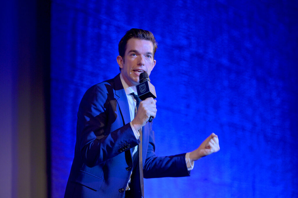 John Mulaney on stage in a navy suit