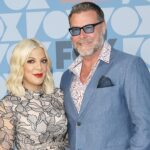Tori Spelling in a black and white dress with Dean McDermott in a blue suit