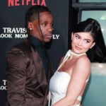 Travis Scott in a brown suit with Kylie Jenner in a white dress