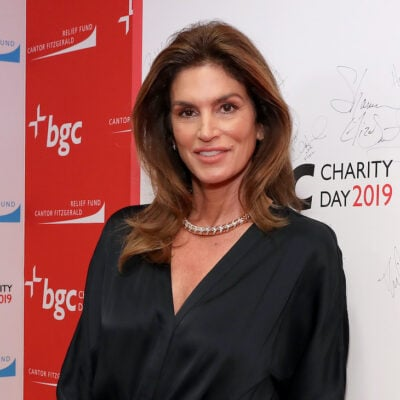 Cindy Crawford smiling in a black blouse