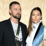 Justin Timberlake in a black jacket and white shirt with Jessica Biel in a white and blue dress