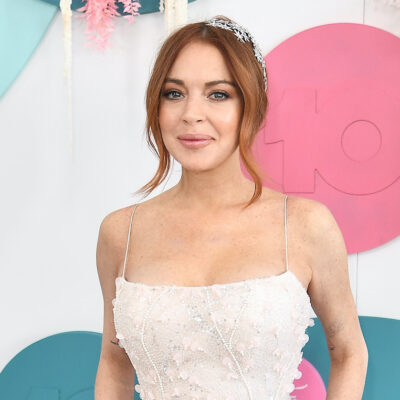 Lindsay Lohan smiling in a white dress