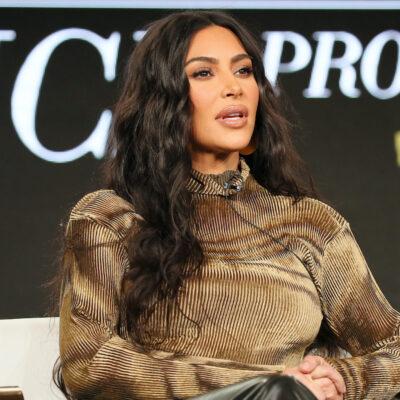 Kim Kardashian in a brown shirt sitting on stage