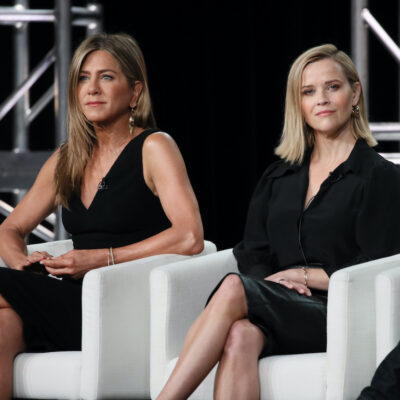 Jennifer Aniston and Reese Witherspoon sitting on stage in black dresses