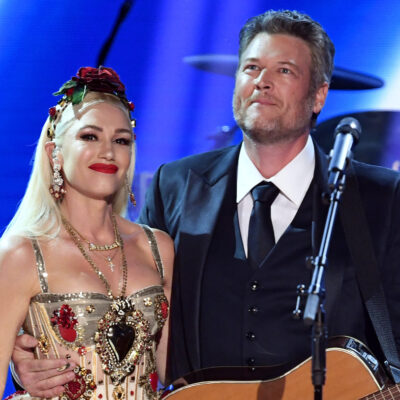 Gwen Stefani in a colorful dress on stage with Blake Shelton in a black suit