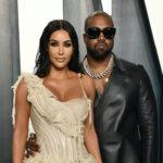 Kim Kardashian in a tan dress with Kanye West in a black jacket